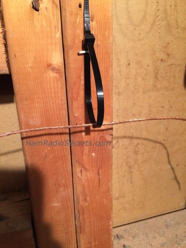 Tie wrap anchoring loop for an attic shortwave antenna.