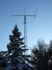 A heavy-duty ham radio tower supporting a large multi-band, multi-element HF yagi.